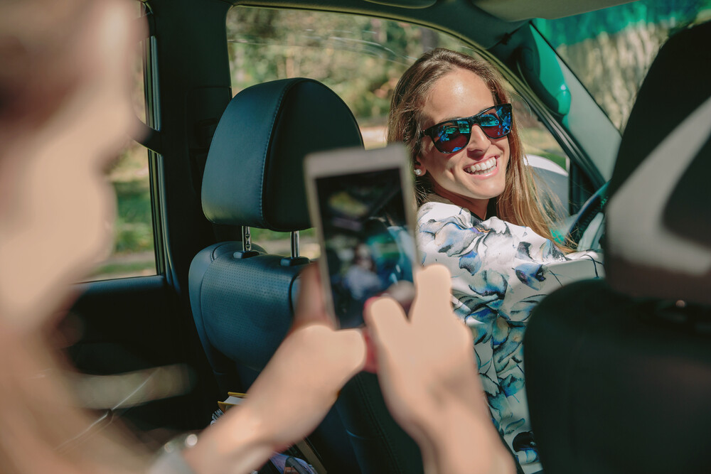 Two women taking photos in their new car for Instagram