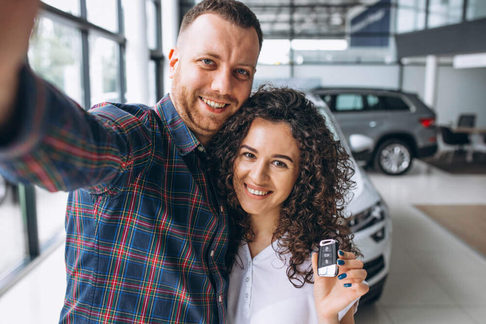 Couple takes a selfie in front of their new car purchase