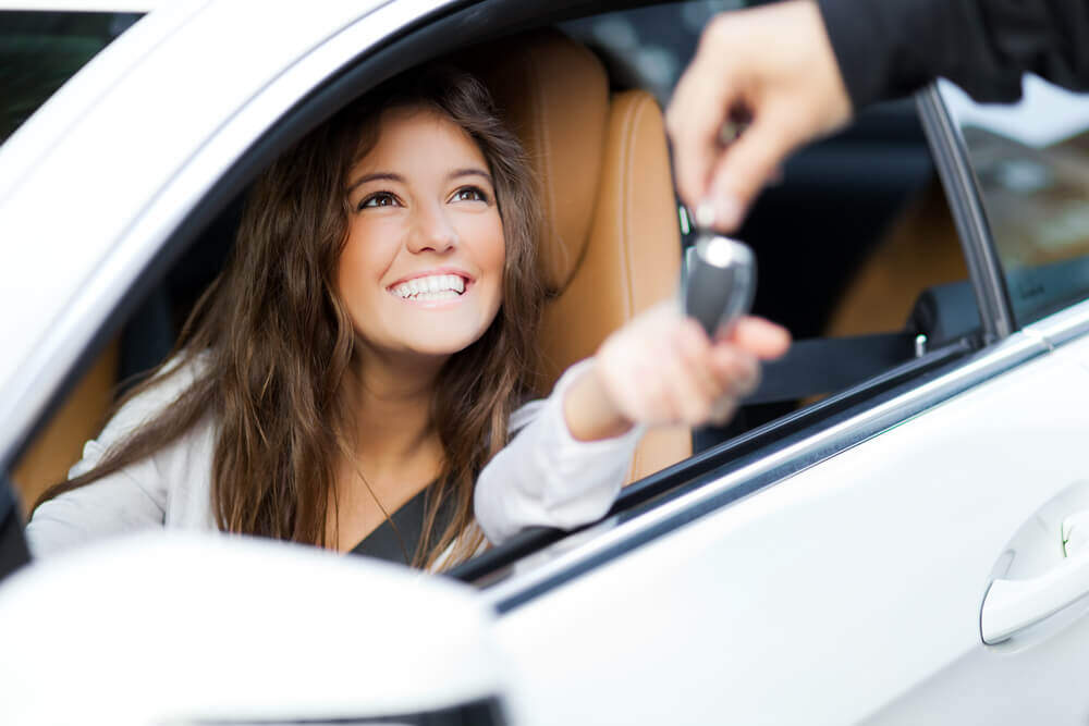 young woman driving away in her new car