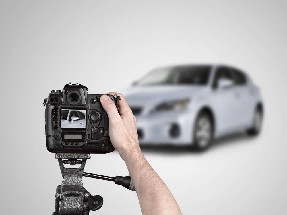 Hand holding a camera photographing a car in a studio