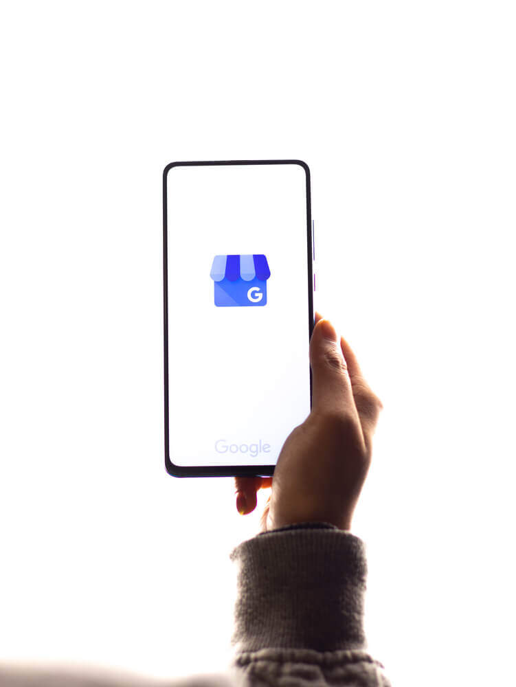 Hand holding a smartphone showing Google My Business Icon